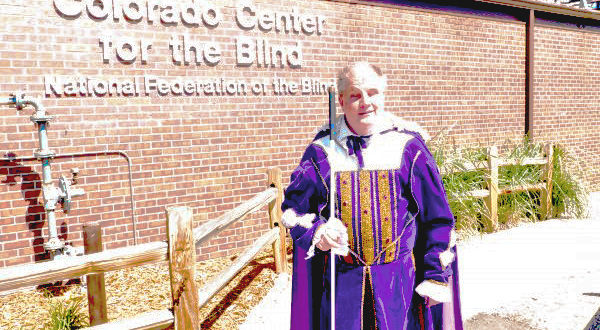 Tom Anderson in a latter-day purple velvet suit beside CCB's sign