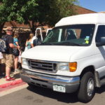 A group of students with shopping bags are lined up to get into the Center's 12 passenger van
