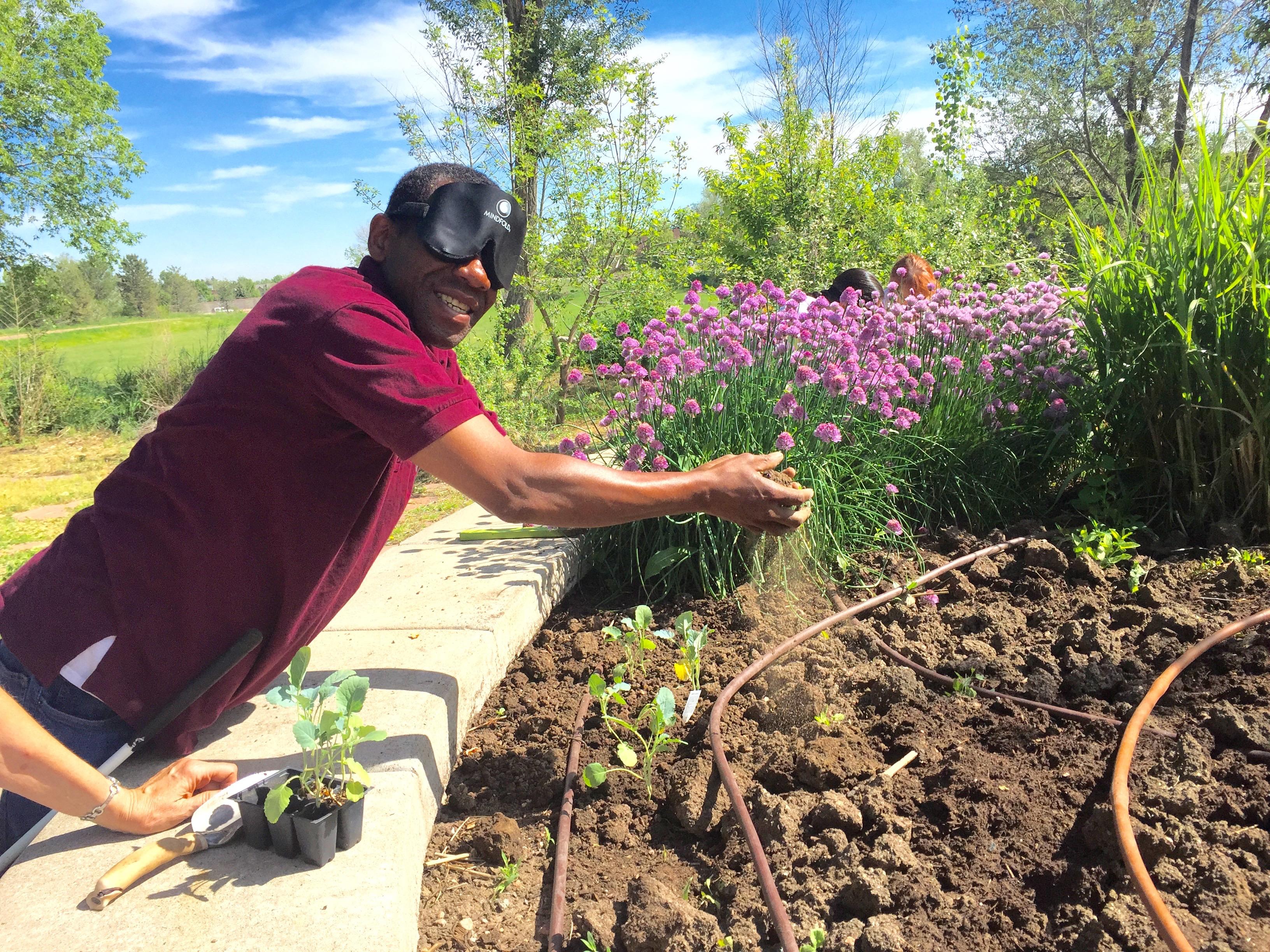 Man wearing sleepshades breaks clods of soil between his hands