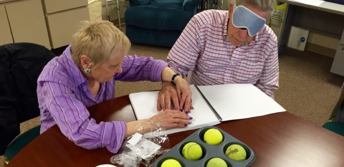 A senior woman and man explore a Braille cell with touch