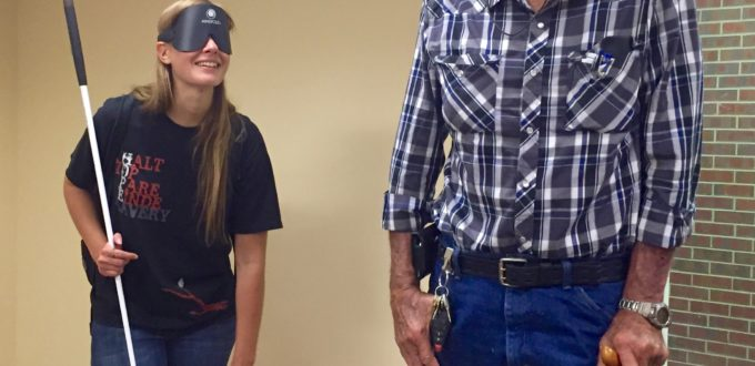 Woman in sleepshades shows visitor a Tech Lab