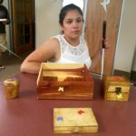 Cindy stands behind her woodshop project. The large box is in the center with the smaller boxes arranged around it.