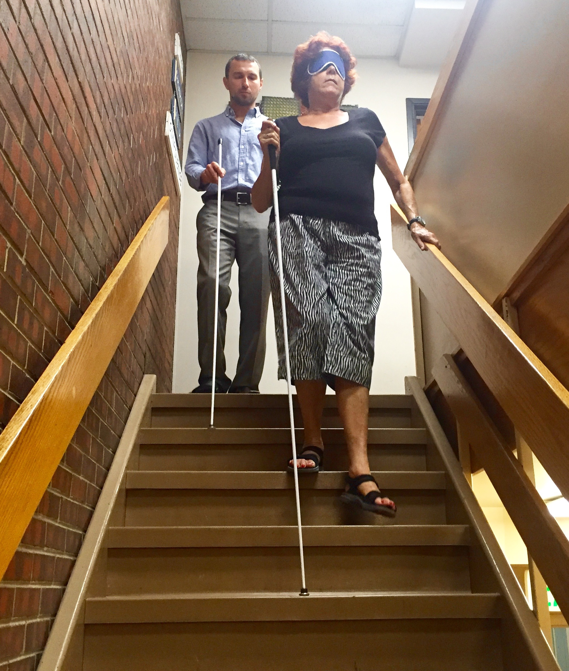 A young man gives a senior woman a cane lesson on the stairs