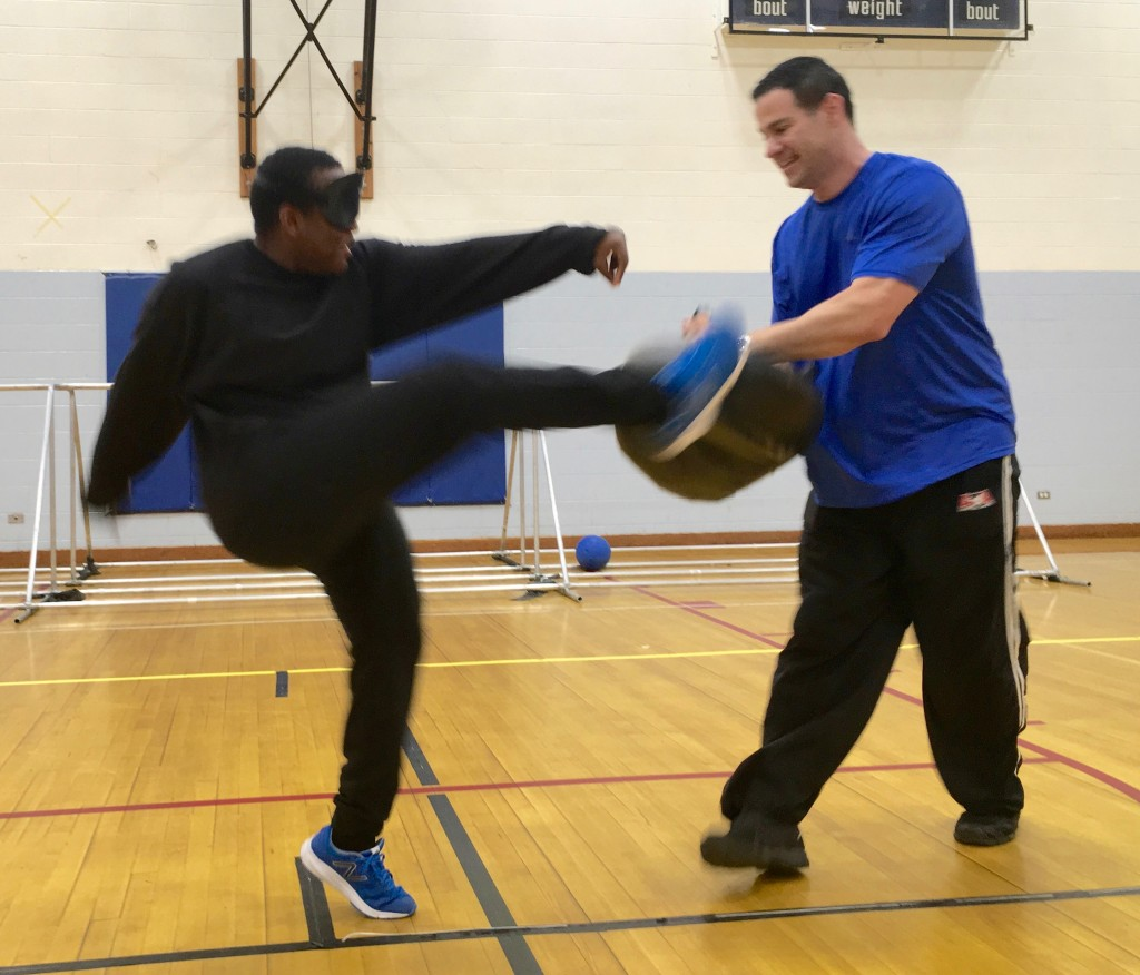 Student makes a High kick into a pad held by his instructor