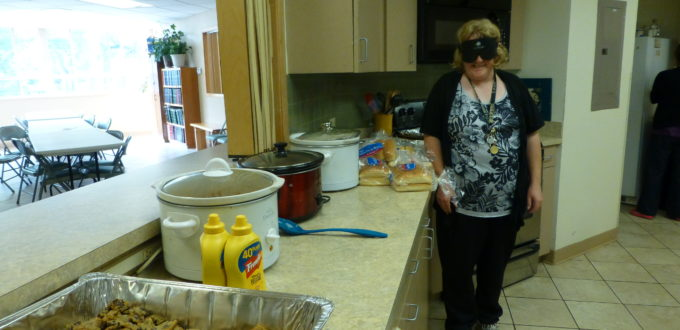Woman wearing sleepshades stands beside a row of hotel pans filled with food