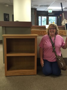 student stands beside her  handsome 3-shelf bookshelf