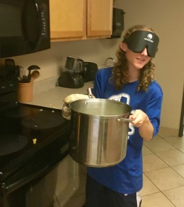 a young woman wearing sleep shades carries a large pot of boiling pasta to the strainer at the sink