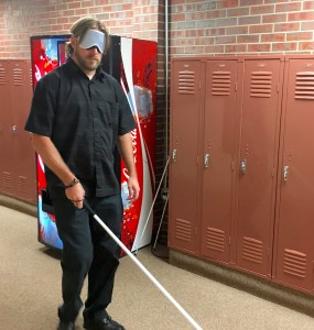 A man with a white cane finds his way past lockers and soda machine wearing sleepshades