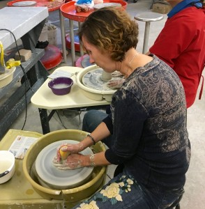 a woman holds a wet sponge against her spinning clay, her other hand stabilizes the base