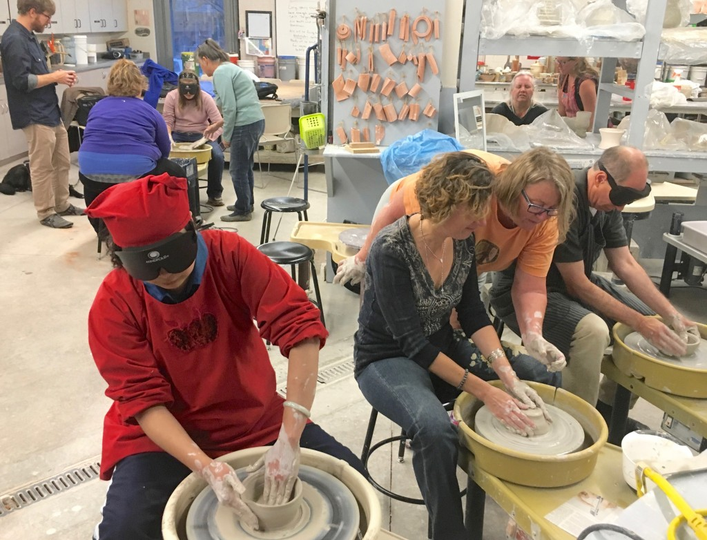 Six people work their clay on pottery wheels