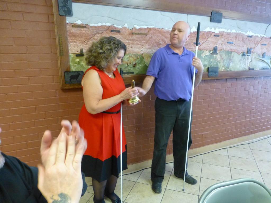A man hands a woman a hand bell