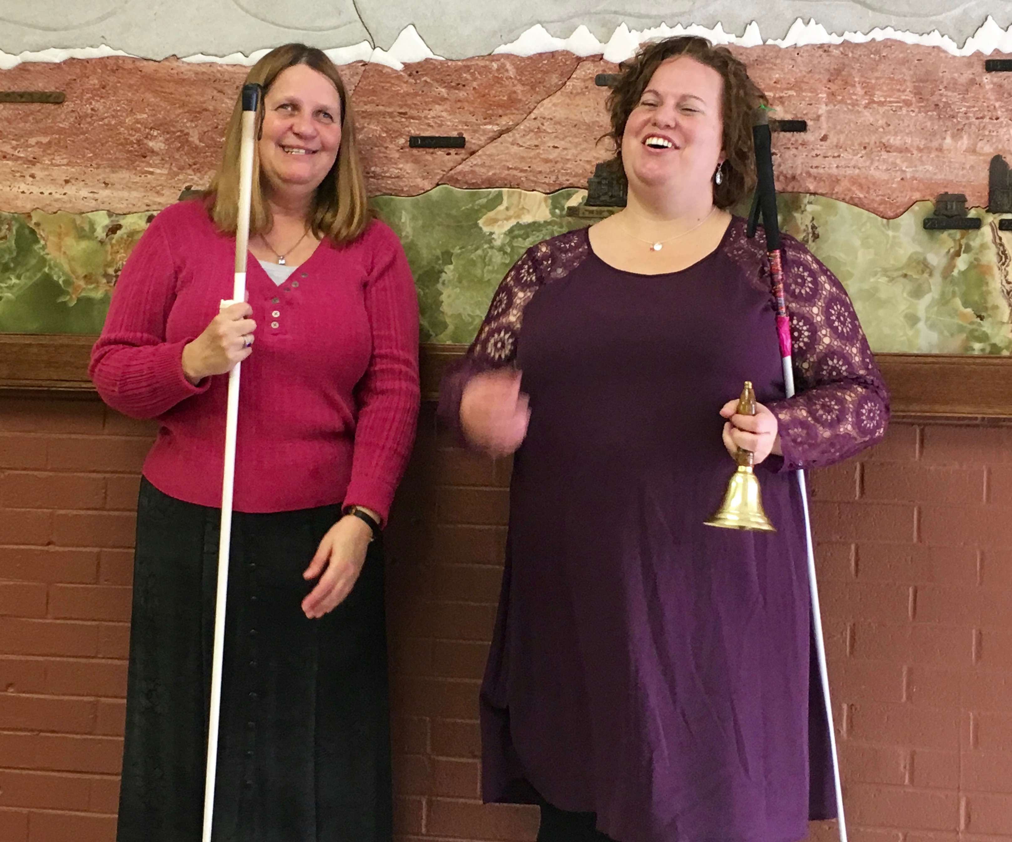 two joyful women stand together, one ringing her Freedom Bell