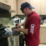 Daniel B. working two large pots on the stove preparing for his mini meal