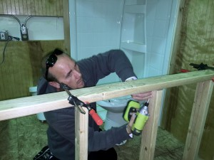 James uses a cordless drill to attach a stud in home maintenance class