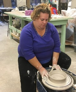 a woman at a potter's wheel puts final touches on her wet clay