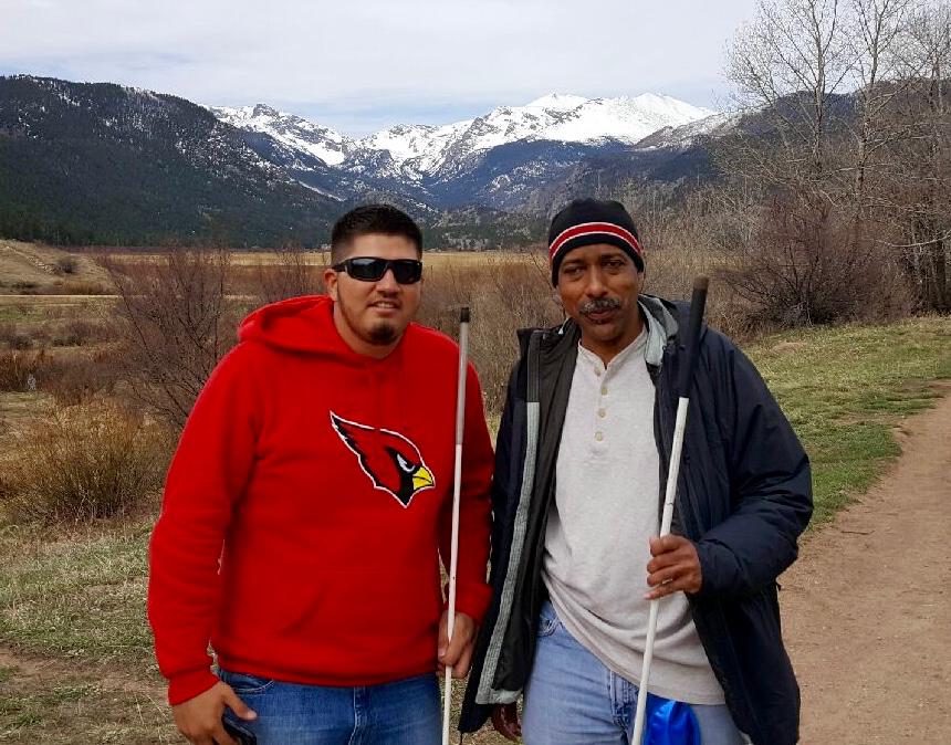 Two men grin at the camera with snowy mountains behind them
