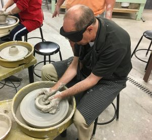 Peter forms a bowl on the potters wheel with both hands cupped around the clay and both thumbs forming the center