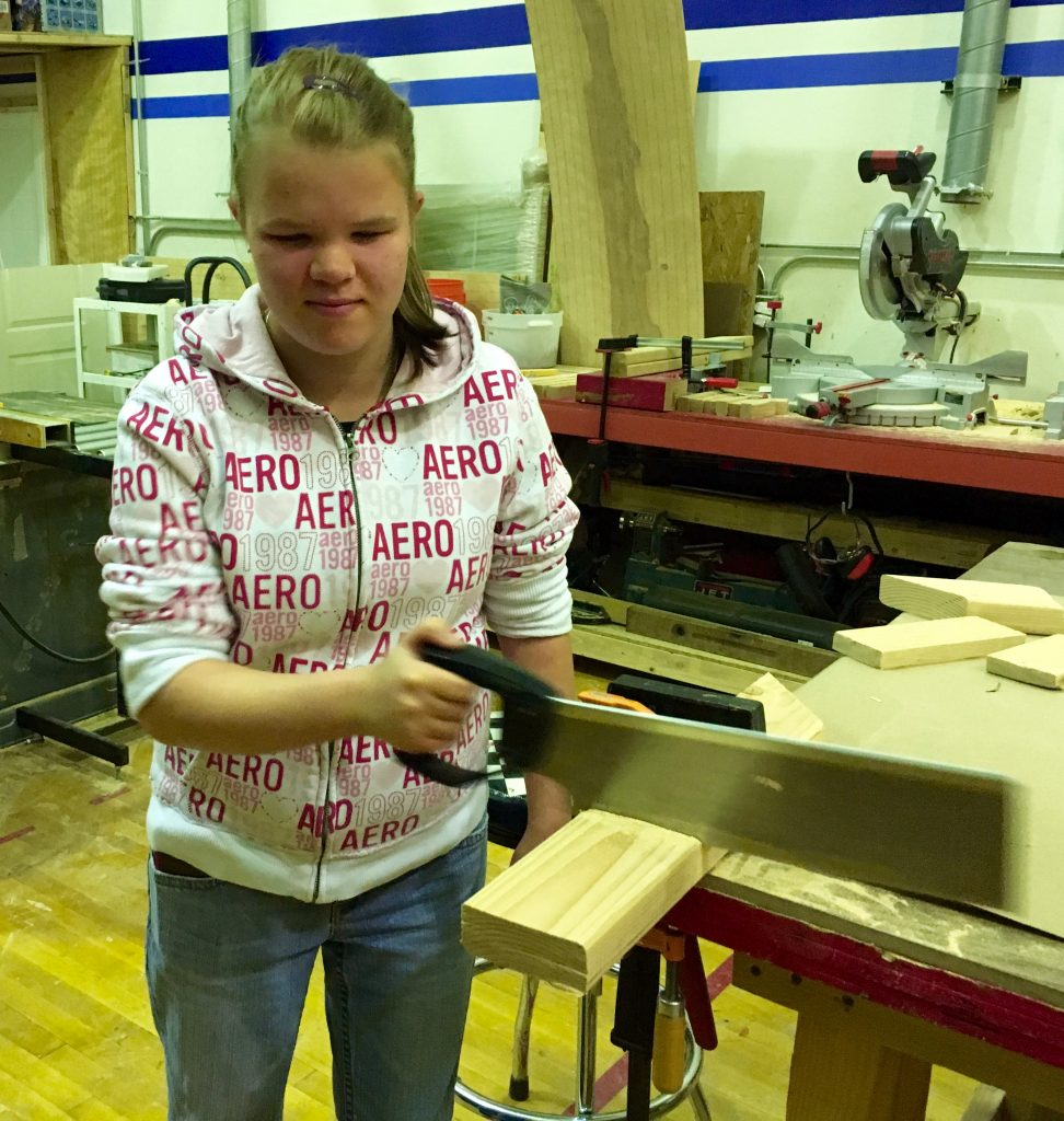 Vika using a hand saw in the woodshop