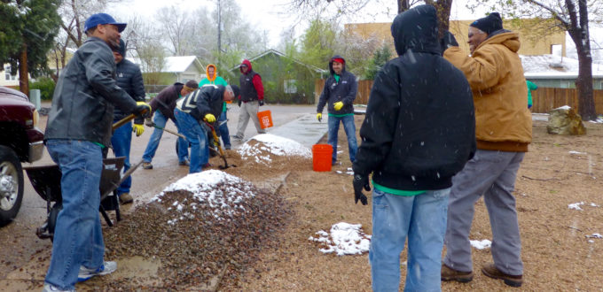 Workers with shoels, rakes and brooms in the snow and rain