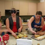 two counselors and two students working on slices of garlic bread