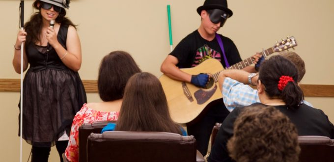 A young woman and young man with guitar perform before a seated crowd. They wear stunning hats.