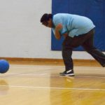 Young man demonstrates a spin throw in Goalball