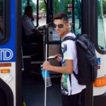 Smiling young man prepares to board the RTD bus