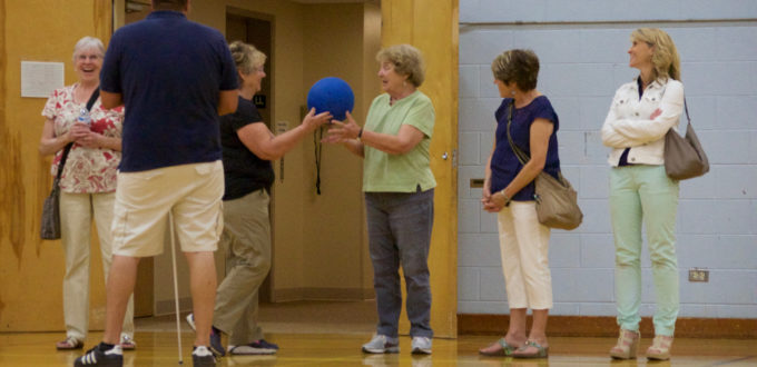 two women at the front of a group toss a a hefty goal ball back and forth