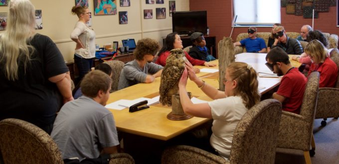 Group shot - The class listens to bird sounds while CG looks at a mount of a Great Horned Owl