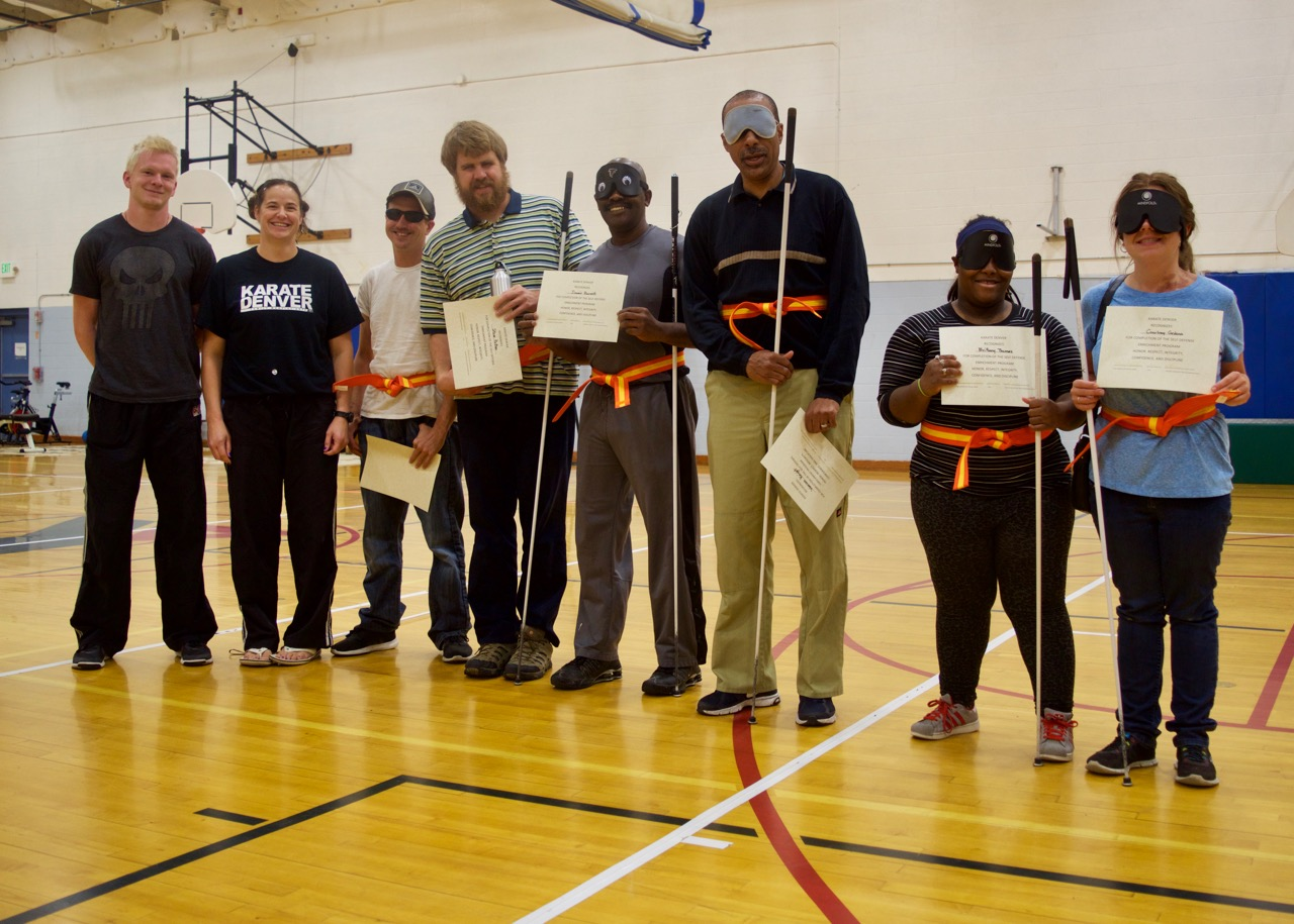 Group shot with instructors standing with the students who are wearing their orange belts and holding their certificates