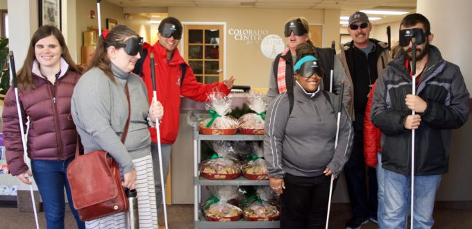 A group of CCB students pose around a cart with six large trays of goodies to give out