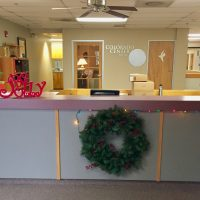 A wreath hanging on the front desk, Christmas lights and wooden ornaments - a Christmas Tree and the word Jolly