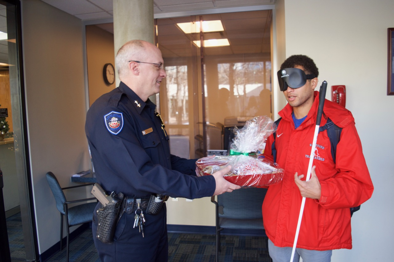 Chaz presents a Christmas basket of items prepared by CCB students to an officer from the Littleton Police Department