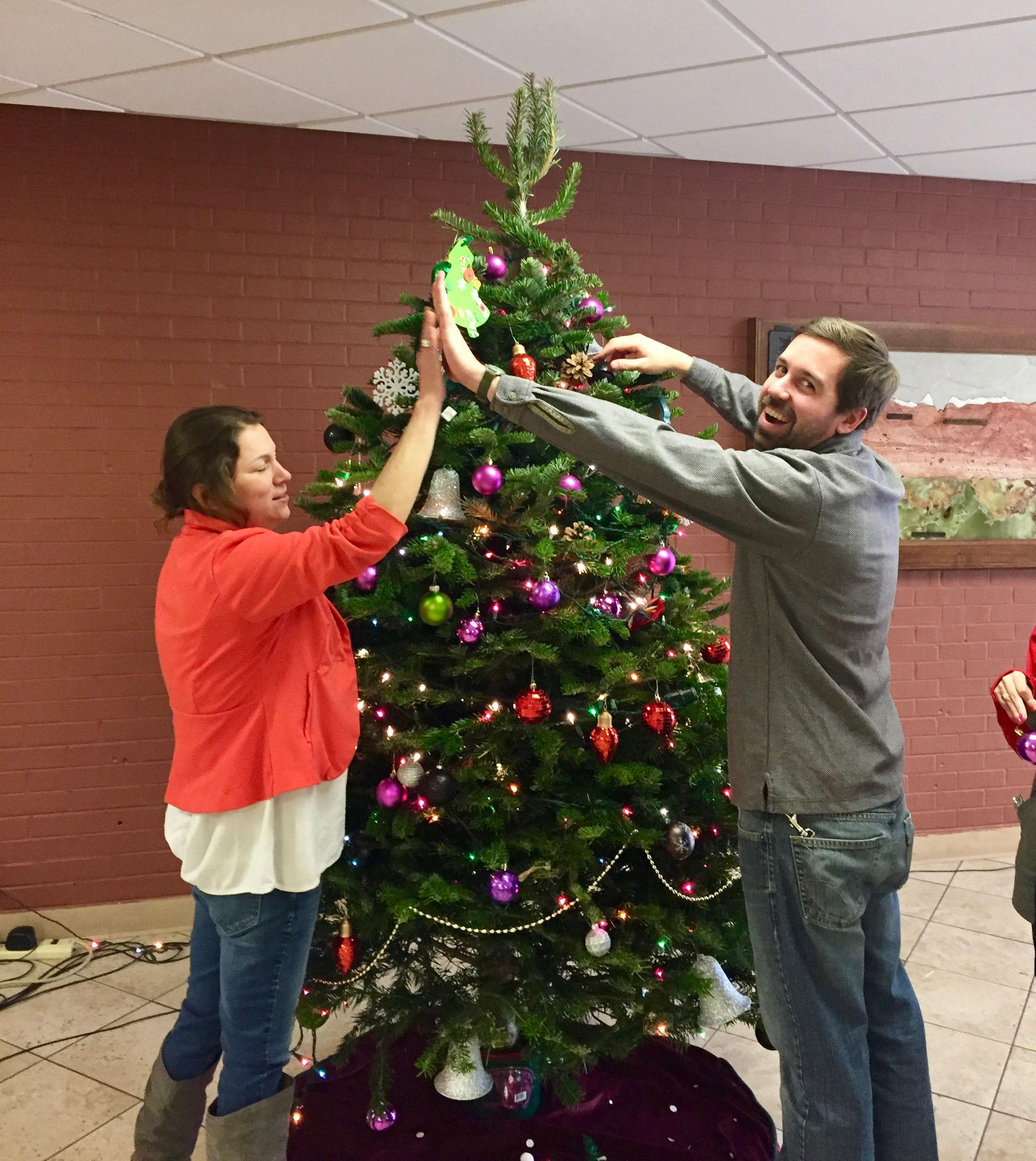 Shop Instructor Chris and Home Management Instructor Delfina high fiving in front of the tree