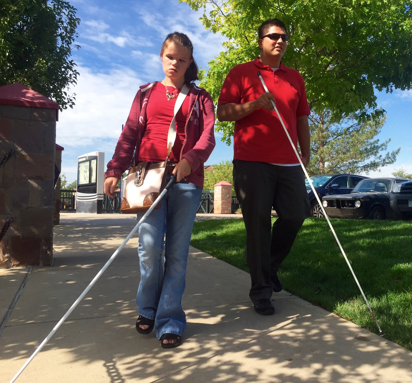 Vika and Martin walk along a shaded sidewalk toward Littleton Downtown Station