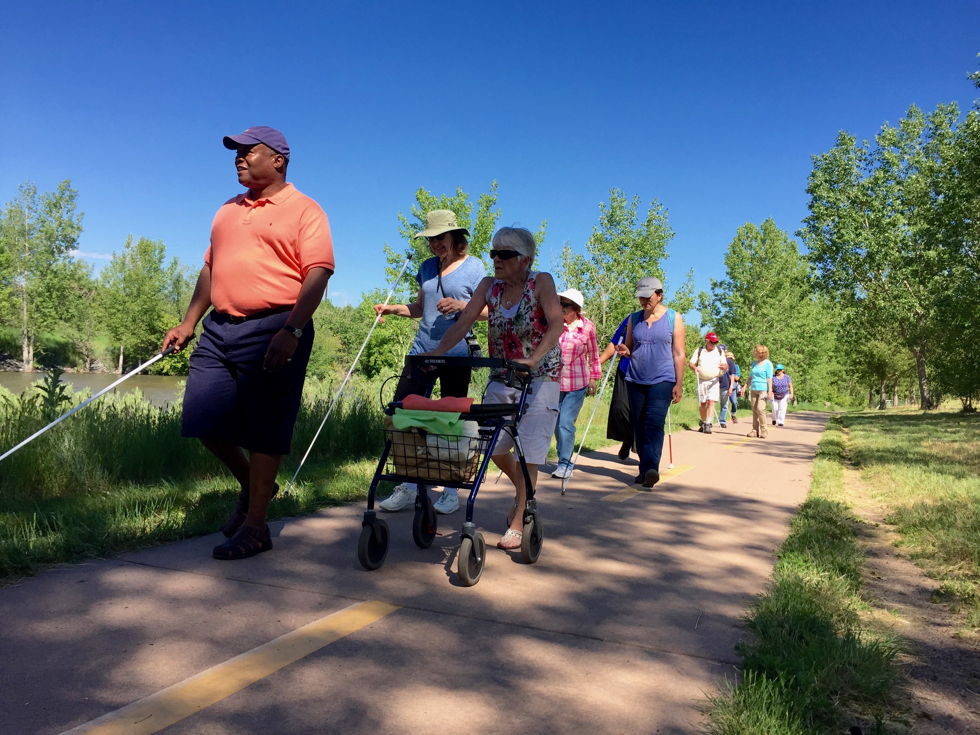 Wayne leads a hike along a river trail with a group of 9 CCB seniors