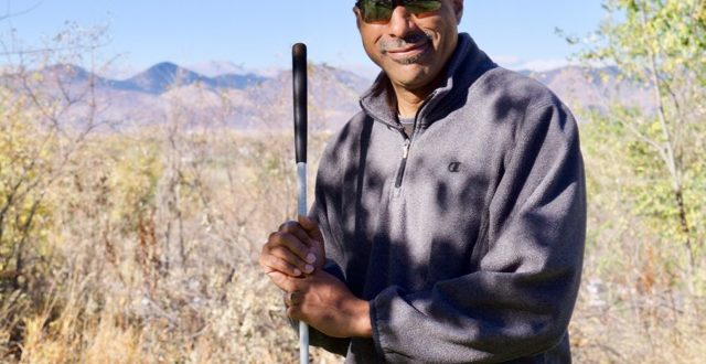 Warren standing with his cane outside the Center with the Mountains in the Background