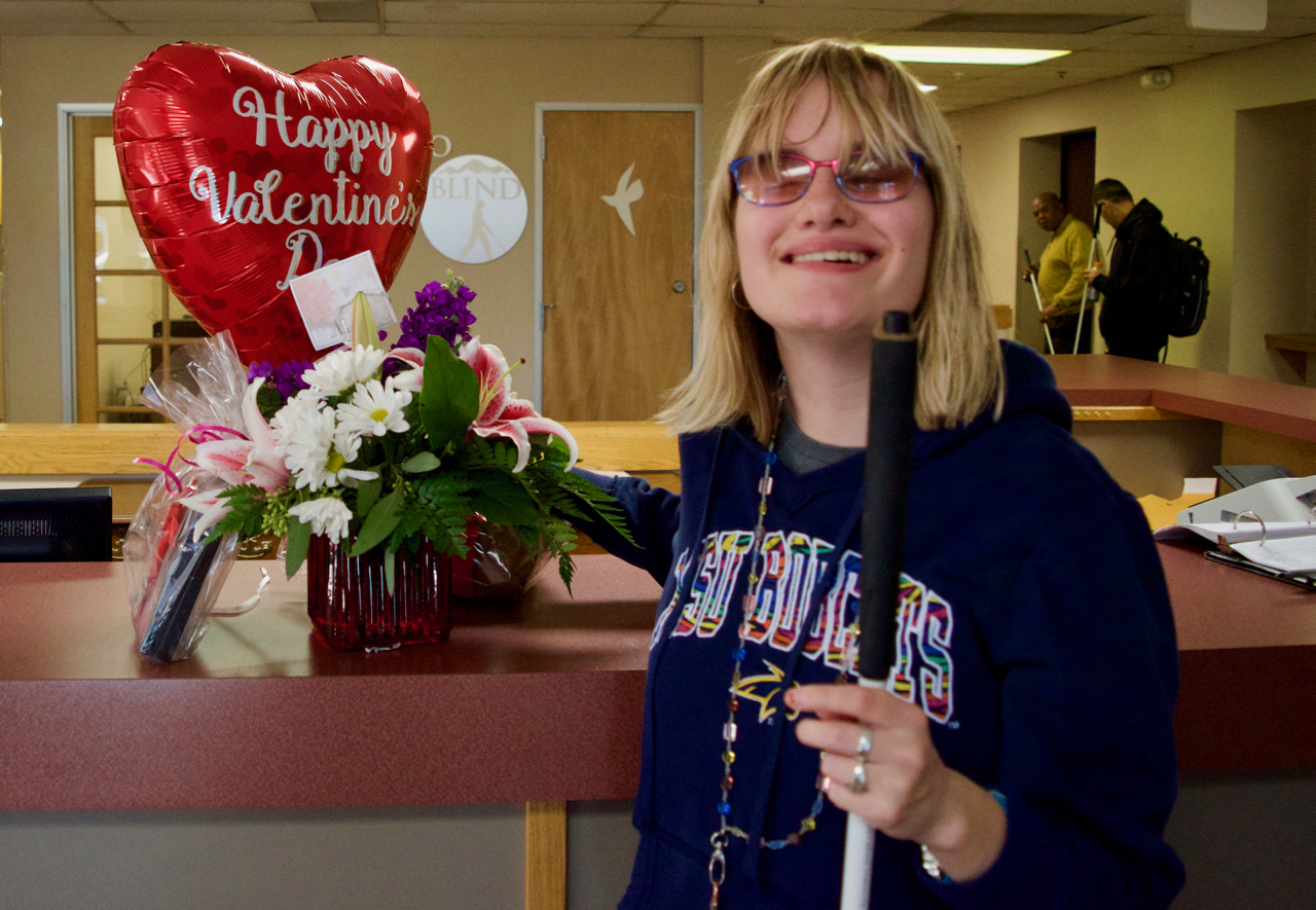 A smiling young woman holds a Happy Valentines Day Heart Shaped Balloon and Flower Arrangement