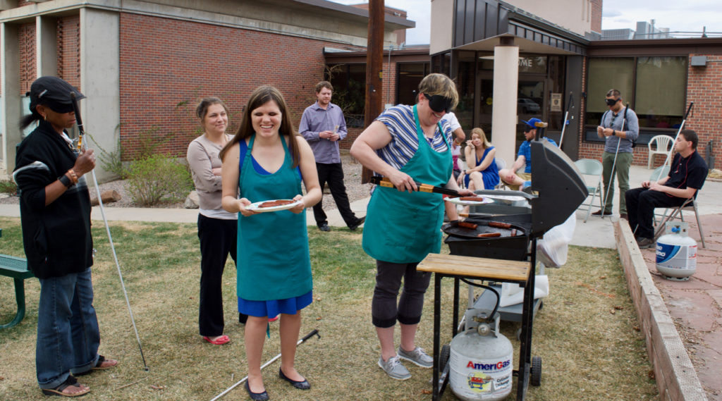 staff and students on the front patio grilling and enjoying the day