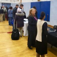 tables in the exhibit area are thronged with job seekers and students