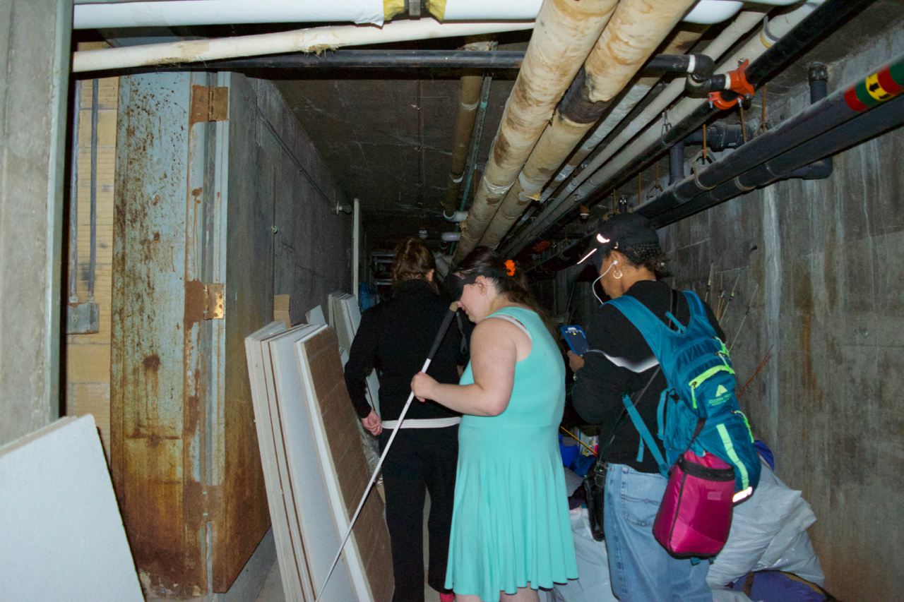 A view of a group of students exploring a tight passage way with lots of pipes and supplies stored along the way