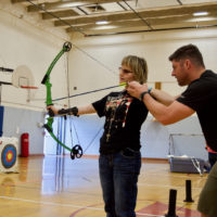 Joy works with Josh on aiming her Bow