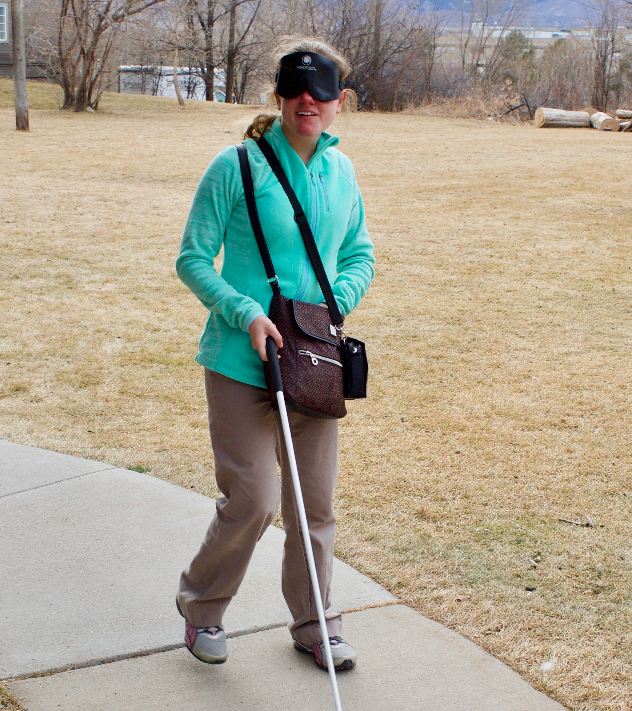 Julie M. traveling with her cane and sleepshades