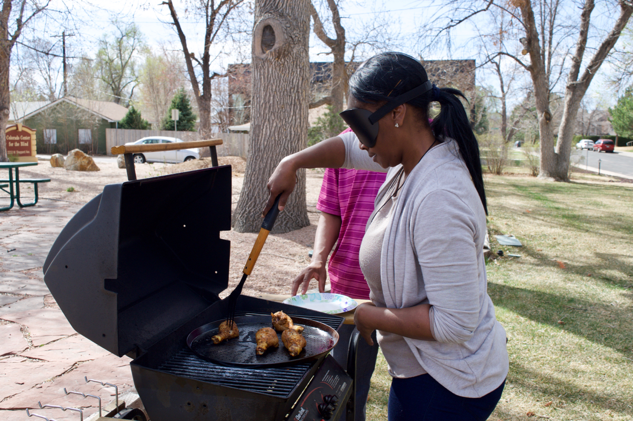 Laura in sleepshades tends chicken on the grill