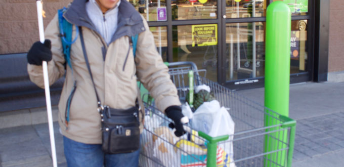 a smiling woman with a cart full of groceries outside the store