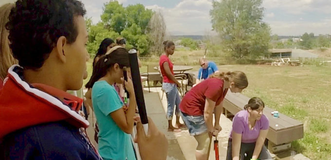 Jamie (bottom right) holding the rocket with a group of CCB youth launching water rockets