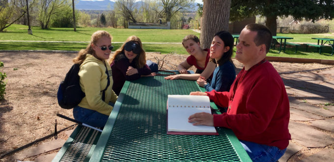 Five people around a picnic table, one reading Braille aloud to the others.