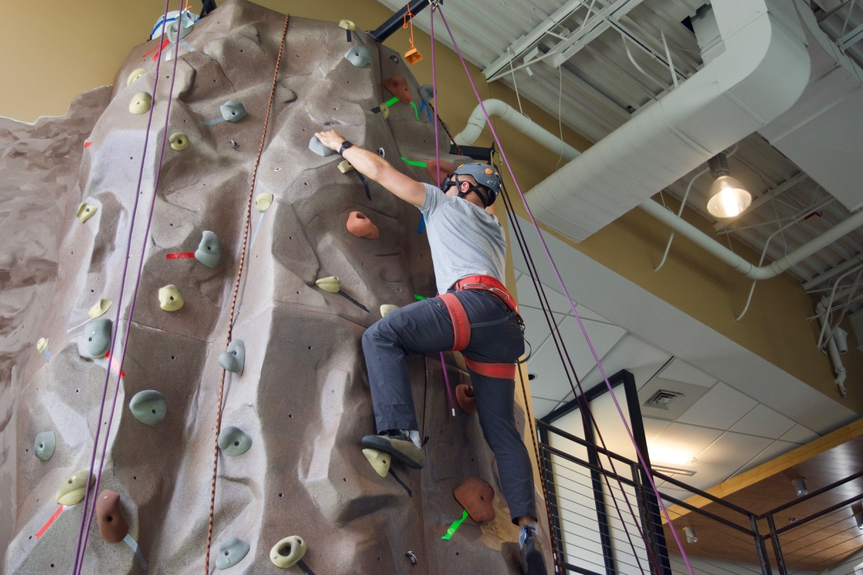 Cezar reaching for a hold as he nears the top of the climing wall