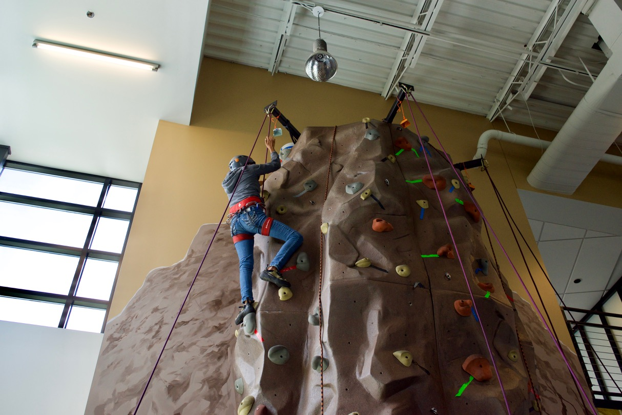 Danielle rings the bell at the top of the climbing wall