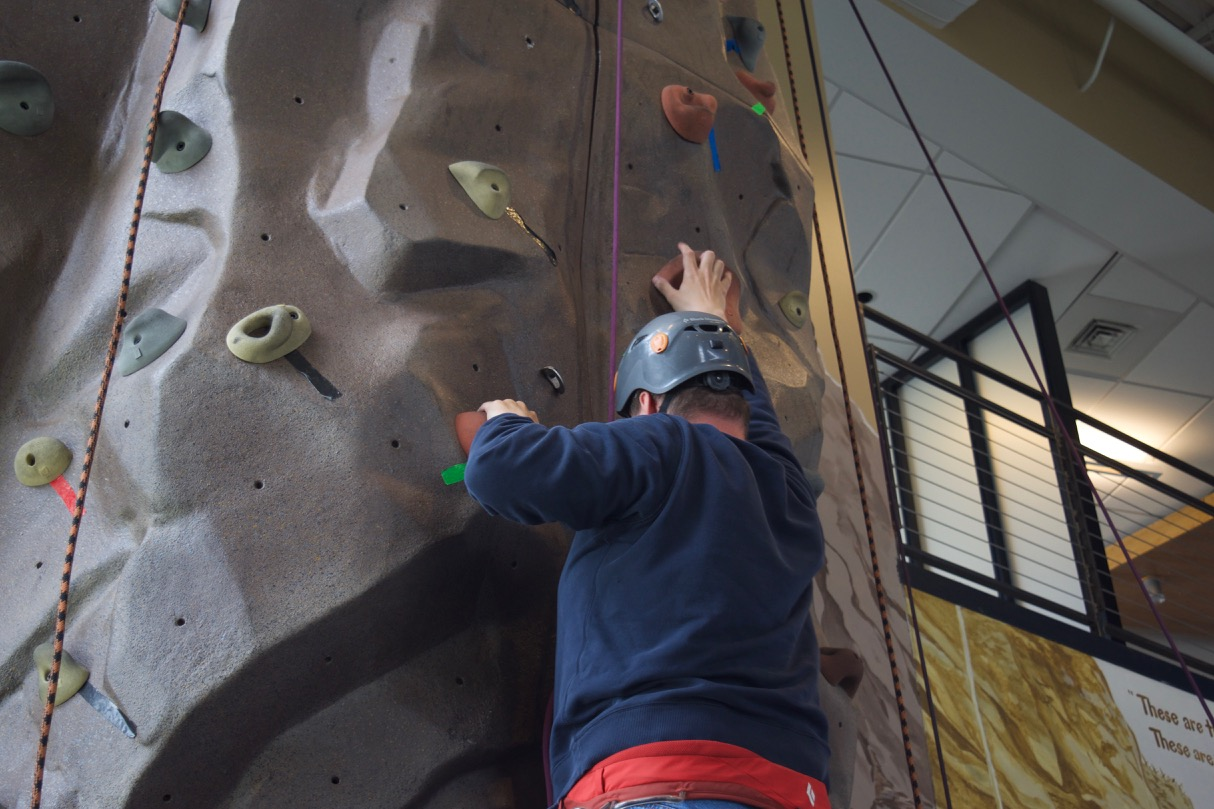 David D. reaches for a handhold as he progresses up the climbing wall